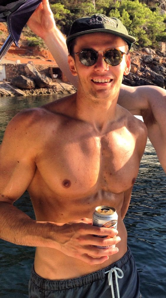 Muscular man on a boat in the sun drinking a beer